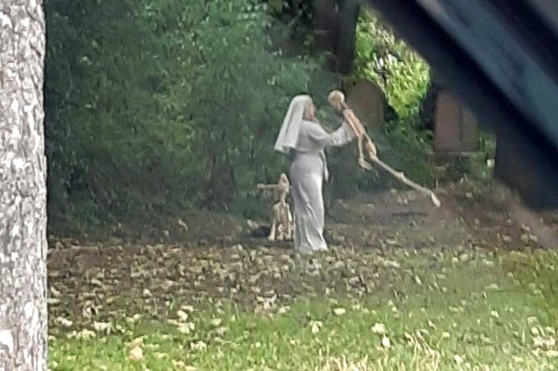 Woman dressed as nun 'dances' with human and dog skeletons next to graveyard